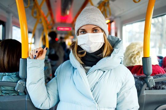 YYoung woman in medical mask standing in bus lounge next to yellow handrails in afternoon.