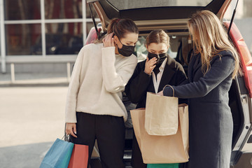 Girls on a shopping. People in a masks. Women with a shopping bags. Lady near trunk of the car. Coronavirus theme. Wall mural