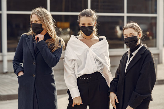 Women in the city. People in a mask. Coronavirus theme. Woman in a white shirt.