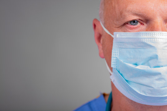 Close up, half face portrait of doctor wearing a surgical mask, against a light background.