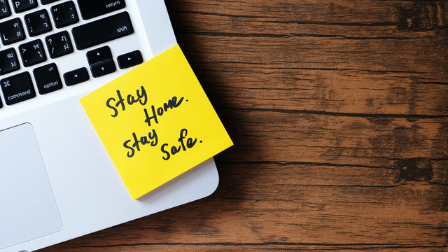 Stay Home. Stay Safe. message concept written post it on laptop keyboard.