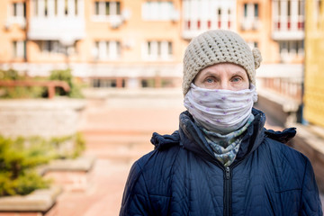 A poor elderly woman wears a homemade mask to protect herself from viruses such as coronavirus, also known as covid-19, or SARS and MERS. She's in an urban environment