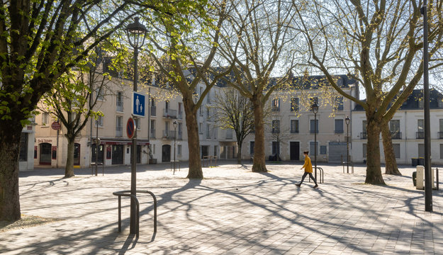 Masked girl walking through empty plaza in Tours, France