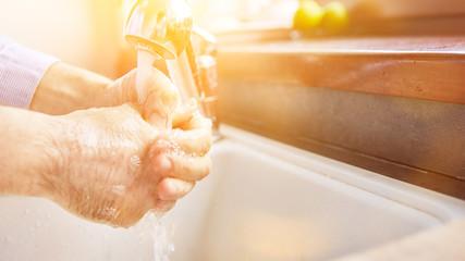 Elderly woman washing hands with soap for coronavirus