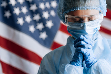 female doctor in a protective medical mask and hat and dressing gown prays against the backdrop of the American flag and asks God for help and strength in the fight against the epidemic of coronavirus Wall mural