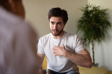 Male client pointing at chest during conversation with psychologist