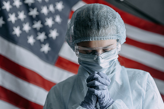 young nurse in a protective medical mask and hat and dressing gown prays against the backdrop of the American flag and asks God for help and strength in the fight against the coronavirus epidemic
