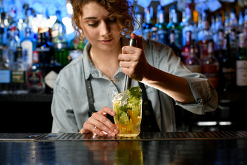 Young woman barman accurate preparing cocktail with slices of citrus fruits