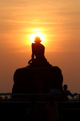 silhouette of a statue of ghandi sitting on a rock in the sunset