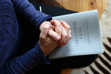 woman's hands folded in prayer while resting on a bible