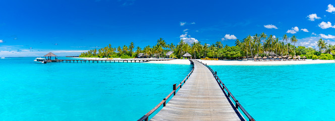 Foto auf Gartenposter Turkis Maldives island beach panorama. Palm trees and beach bar and long wooden pier pathway. Tropical vacation and summer holiday background concept