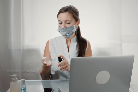 Caucasian woman wearing medical face mask dispensing hand sanitizer into hands while working on laptop at table. Working remotely on quarantine in case of COVID-19. Coronavirus social distancing conta
