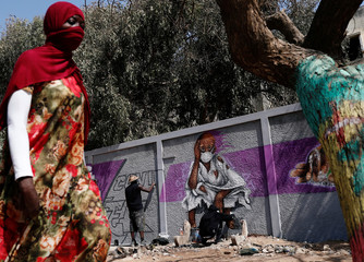 A woman walks past graffiti artists from RBS crew as they work on their mural to encourage people to protect themselves amid the outbreak of the coronavirus disease (COVID-19), in Dakar
