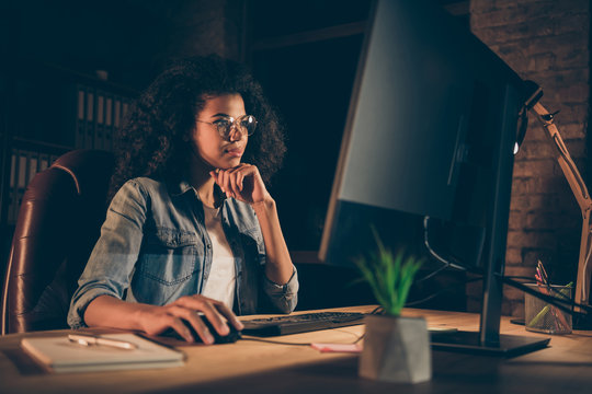 Photo of young dark skin business lady look big screen monitor check id-address working overtime wear specs casual denim shirt sitting table chair late night office indoors