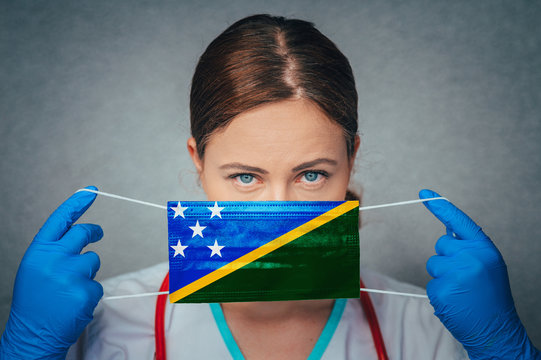 Coronavirus in Solomon Islands Female Doctor Portrait hold protect Face surgical medical mask with Solomon Islands National Flag. Illness, Virus Covid-19 in Solomon Islands , concept photo