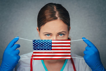 Coronavirus in United States of America, USA, Female Doctor Portrait hold protect Face surgical medical mask with America, USA National Flag. Illness, Virus Covid-19 in USA, concept photo