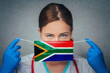 Coronavirus in South Africa Female Doctor Portrait hold protect Face surgical medical mask with South Africa National Flag. Illness, Virus Covid-19 in South Africa, concept photo