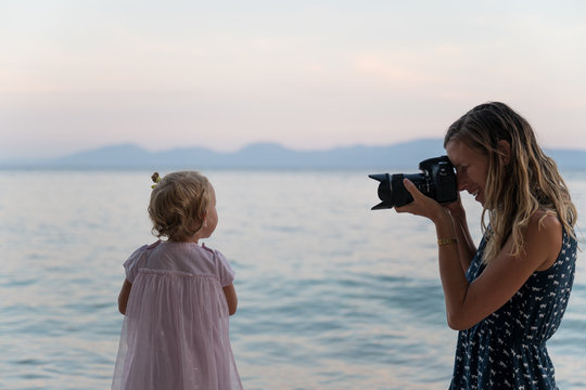 Mother taking photo of her daughter on the beach