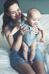 Mom sits on the couch and holds in her arms her baby son with a funny facial expression