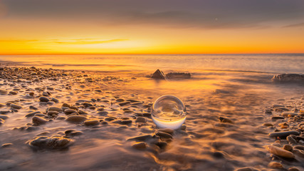 Foto auf Gartenposter Cappuccino Boule de cristal sur des galets d'une plage au lever de soleil.