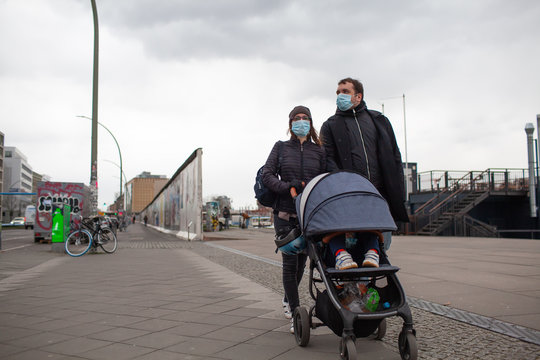 Young Caucasian family in surgical masks walking with baby outdoor in Berlin. Protective face mask precaution against new Chinese atypical pneumonia COVID-19 epidemic virus disease.