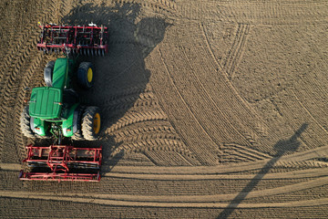 A French farmer drives his tractor to prepare the land before sugar beets sowing in Anneux