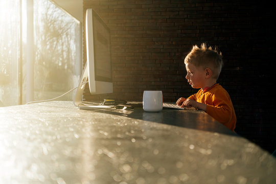 little child in kindergarten age using desktop computer at home for leisure - alpha generation concept