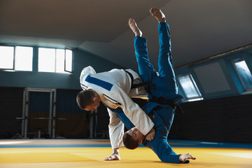 Two young judo caucasian fighters in white and blue kimono with black belts training martial arts in the gym with expression, in action, motion. Practicing fighting skills. Overcoming, reaching target