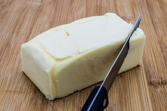 Rectangular clod of butter with a black knife