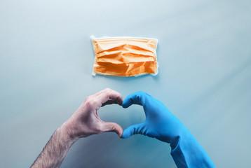 Coronavirus in Italia fine della pandemia, successo con simbolo del cuore fatto dalle mani di un medico. Virus definitivamente debellato. Vista alto, livello piatto.
