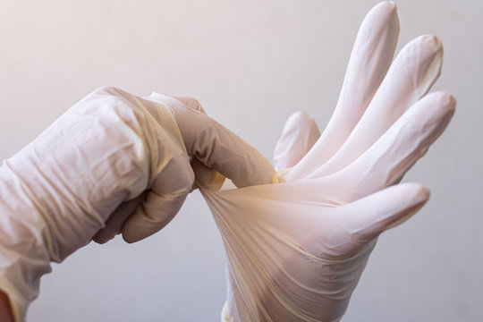 Women's hands with latex gloves, removing gloves safely and effectively to avoid contagion.