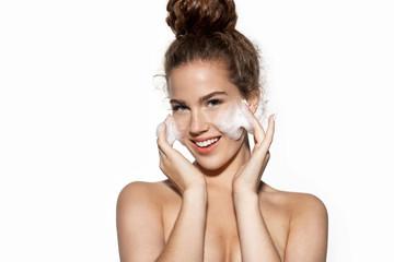 Fototapeta Girl enjoy facial skin cleansing procedure  massaging cheeks