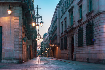 Narrow cobbled medieval empty street with beautiful street lights in Barri Gothic Quarter in the morning, Barcelona, Catalonia, Spain