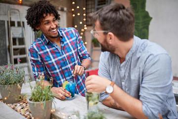 Two male friends socializing in cafe outside Fotomurales
