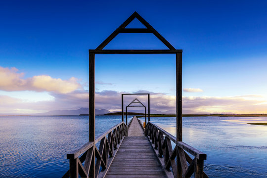 A Bridge going over the ocean in Mulranny, Westport Co Mayo, Ireland on a beautiful evening. A clear blue sky and some waves in the water with the way in the center.
