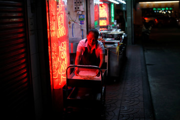 A woman removes food from outside a restaurant in an empty street in Bangkok