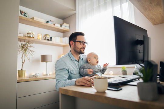 Young father working from home and babysitting his baby boy in the same time.