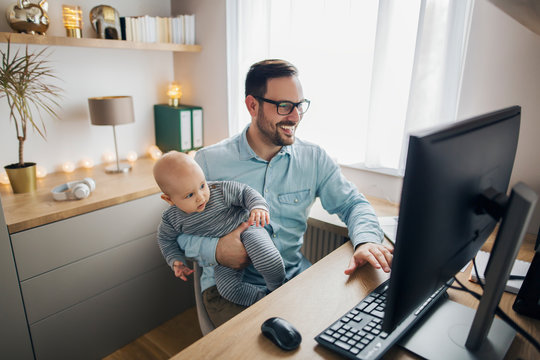 Young parent works from home and holds his baby boy.