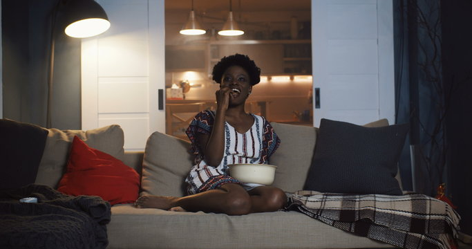 Happy young casual African woman sits on couch at home watching movies on projector with drinks and popcorn slow motion.