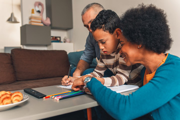 Parents helping their son with his homework at home in living room.