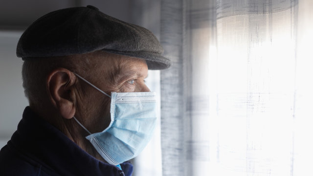 COVID-19 Portrait of an old man with antivirus mask looking at the window