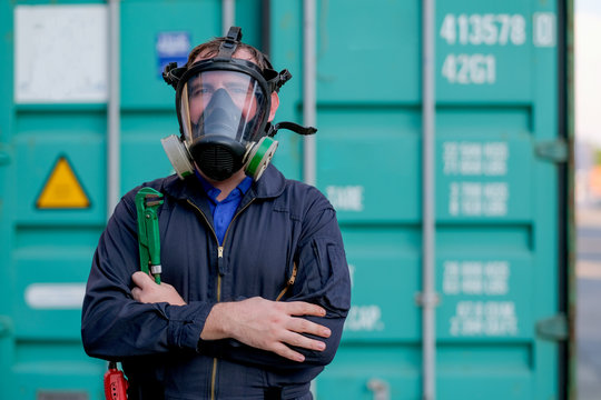 Technician or worker with chemical mask also engineer uniform stand and hold wrench in front of green container workplace and look confident by cross arms or fold over.
