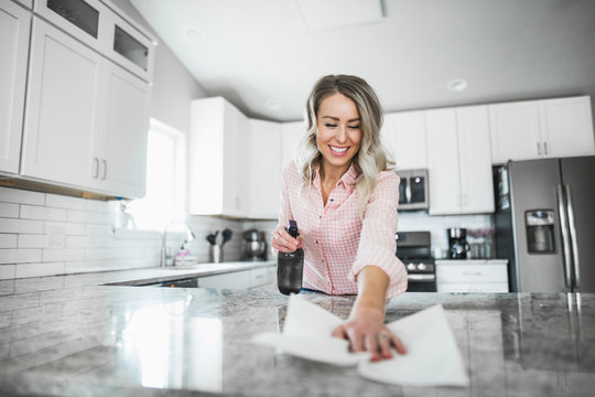 Young woman cleaning her kitchen couters with disinfectant
