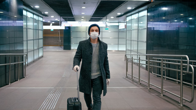 COVID-19 Coronavirus Pandemic Travel Restrictions. Man in Surgical Face Mask Walks with Suitcase in Airport or Train Station
