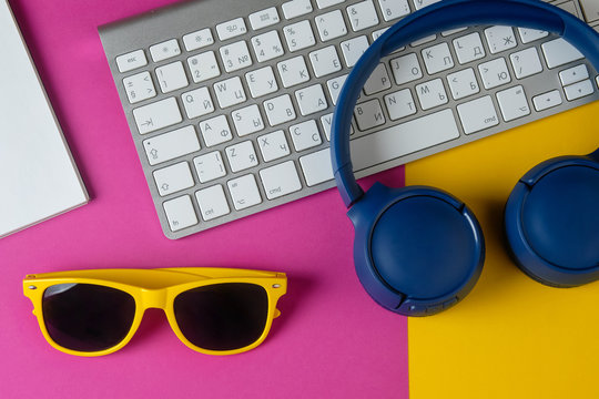 Flat lay composition with headphones, sunglasses, notepad and keyboard on a yellow purple background. Summer work concept.
