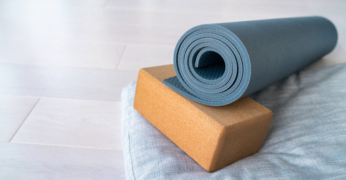 Yoga mat, cork block meditation pillow eco-friendly sustainable fitness products shopping. Natural organic material props for wellness on wooden floor background.