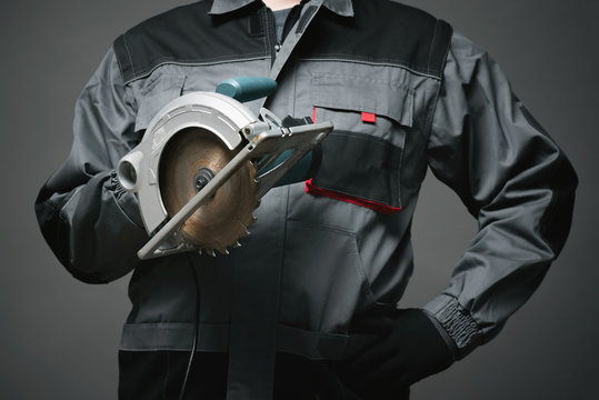 Builder worker with a circular saw in the hand close up on dark background.