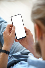Millennial man user holding smart phone mock up white screen in hand using mobile dating app, check...