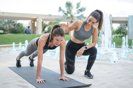 Fitness young woman doing push-ups with assistance of her female personal trainer outdoors