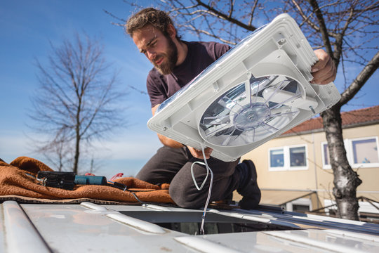 Man installing a fan on the roof of his camper van